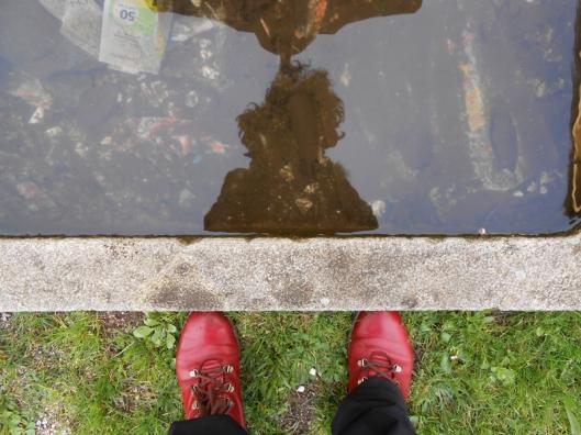 """""""Los pies en la tierra"""": mi imagen reflejada en el remanso de una fuente contaminada."""